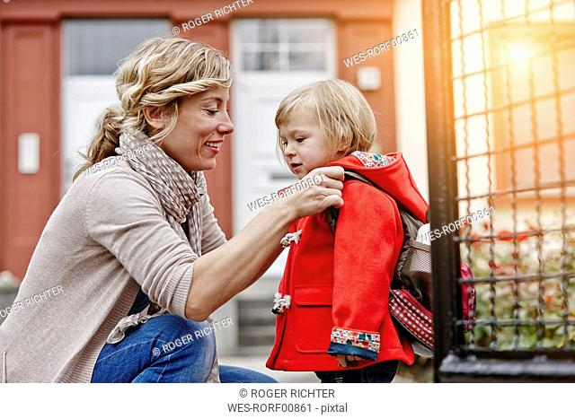 Mother with daughter at house entrance