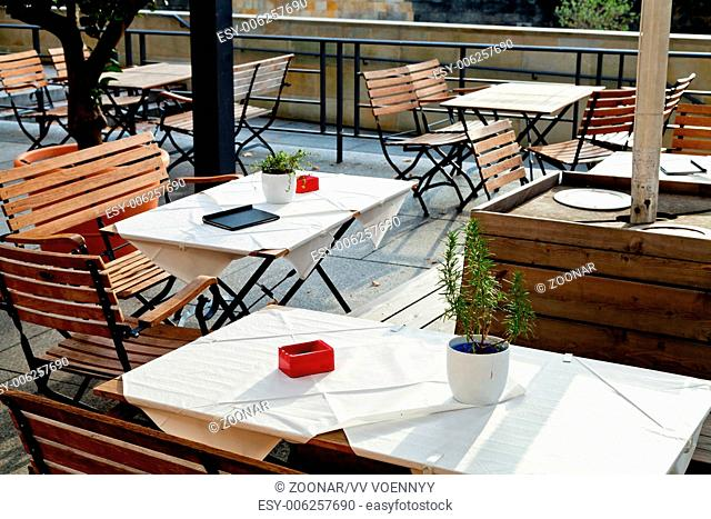 empty outdoor tables of waterfront restaurant