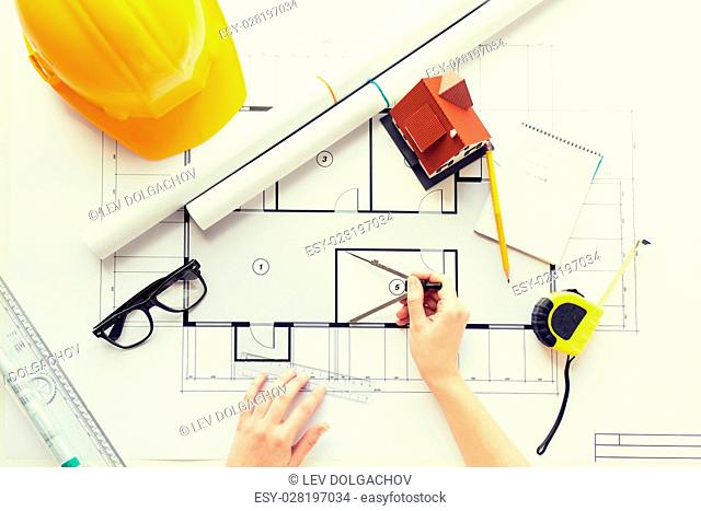 business, architecture, building, construction and people concept - close up of architect hands with compass measuring living house blueprint