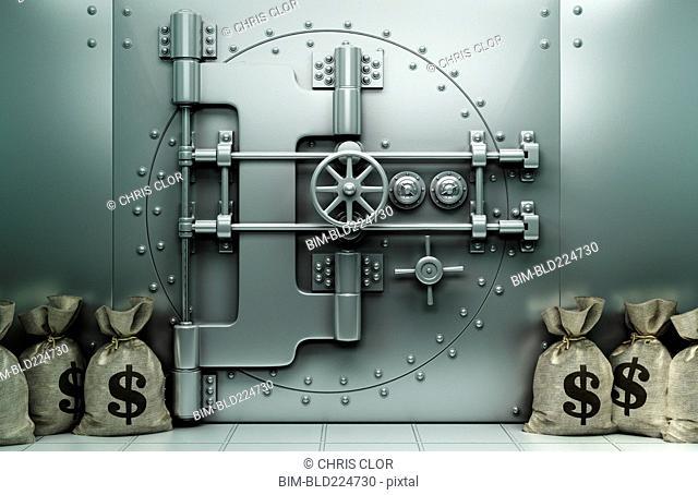 Money bags with dollar symbol on floor near vault