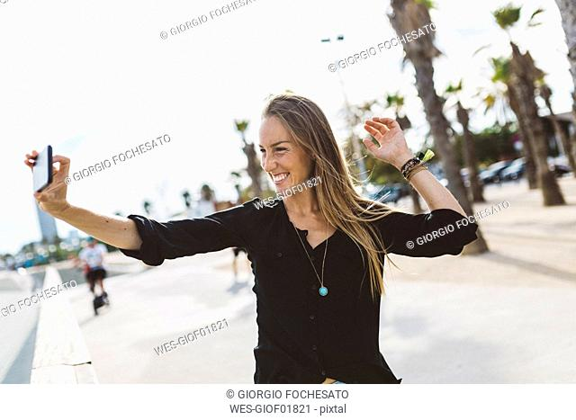 Happy young woman taking a selfie on waterfront promenade