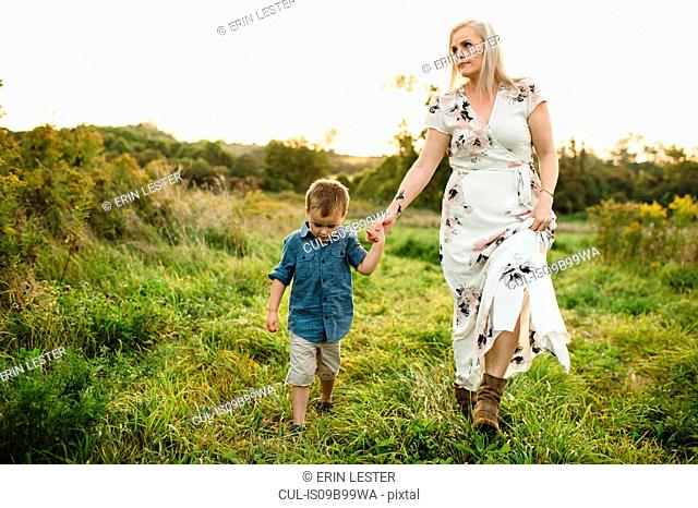Mother and son walking on grass holding hands