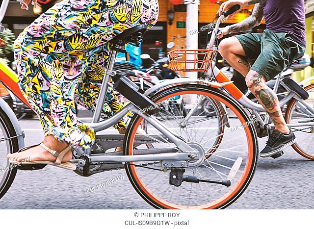 Waist down view of multi ethnic hipster couple cycling along street, Shanghai French Concession, Shanghai, China