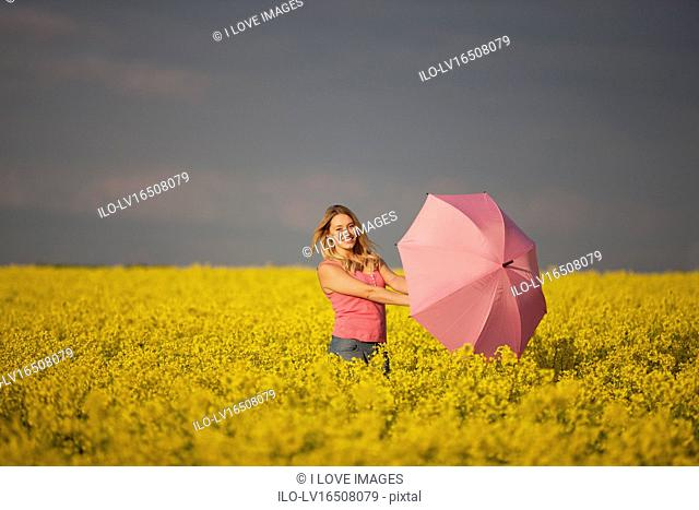 A young woman standing in a rape seed field holding a pink umbrella