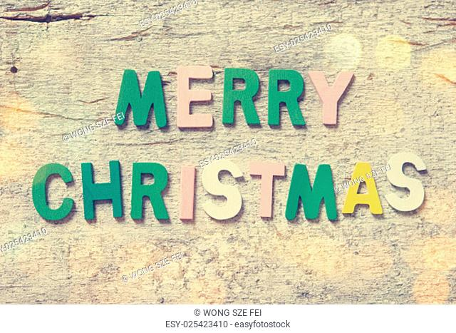 """The colorful words """"""""MERRY CHRISTMAS"""""""" made with wooden letters on old wooden board"""