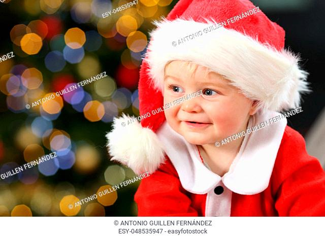 Portrait of a baby wearing santa disguise looking at side on a couch at home with a tree and lights in the background