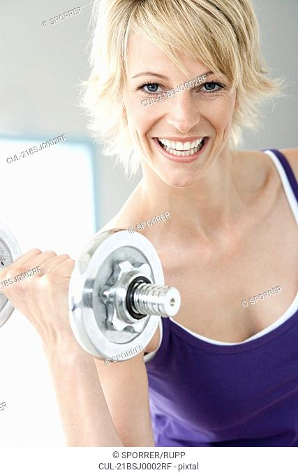 Woman with dumbbell smiling to camera