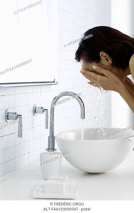 Woman leaning over bathroom sink washing face, side view