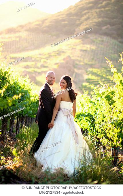 Happy couple walking in a vineyard surrounded by mountains, looking back. Saddlerock winery, Malibu, CA