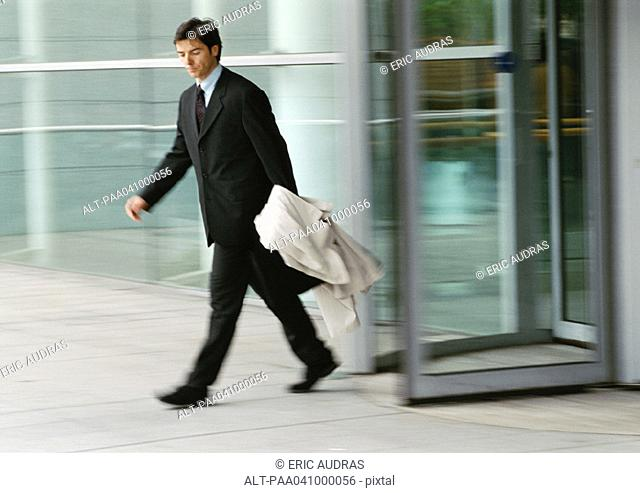 Businessman leaving building, holding overcoat, blurred