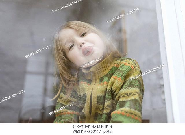 Portrait of little girl sticking out tongue while looking out of window