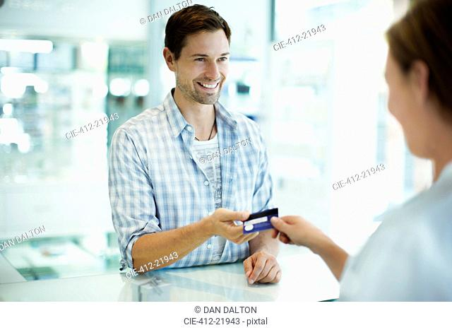 Man paying with credit card in drugstore