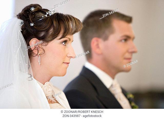 Junges Brautpaar schaut aufmerksam nach vorne