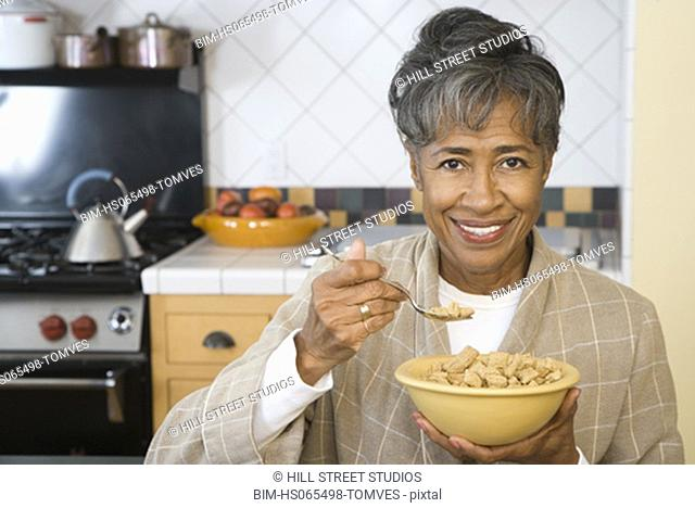 Senior African woman eating breakfast