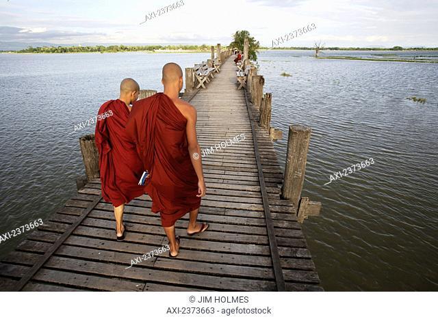 Buddhist monks walk across U Bein Bridge, made of Teak wood; Mandaly, Burma