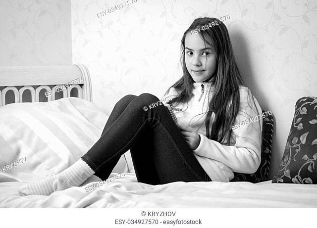 Black and white portrait of teenage girl making notes in diary