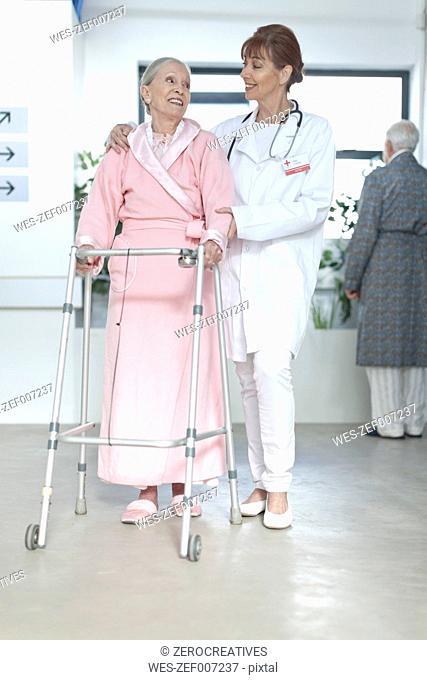 Doctor leading elderly patient with walking frame on hospital floor