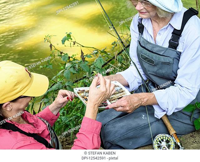 Women sorting lures for fly fishing, Gunpowder Falls River; Monkton, Maryland, United States of America