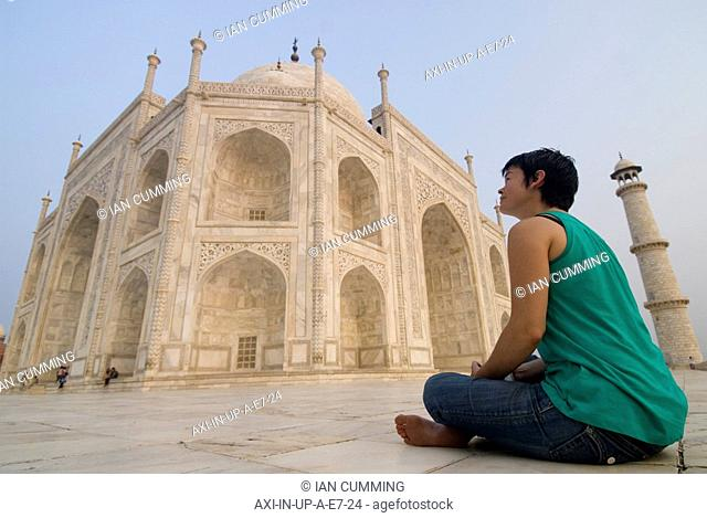 Woman sitting on ground admiring the Taj Mahal at dawn