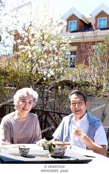 The old couple drink tea in the courtyard