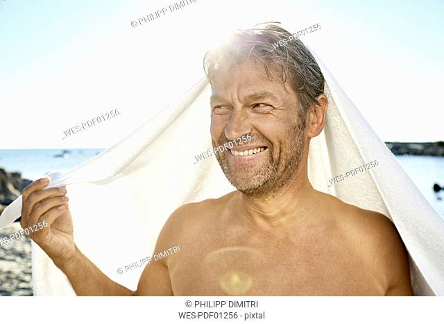 Portrait of smiling man with towel in front of the sea