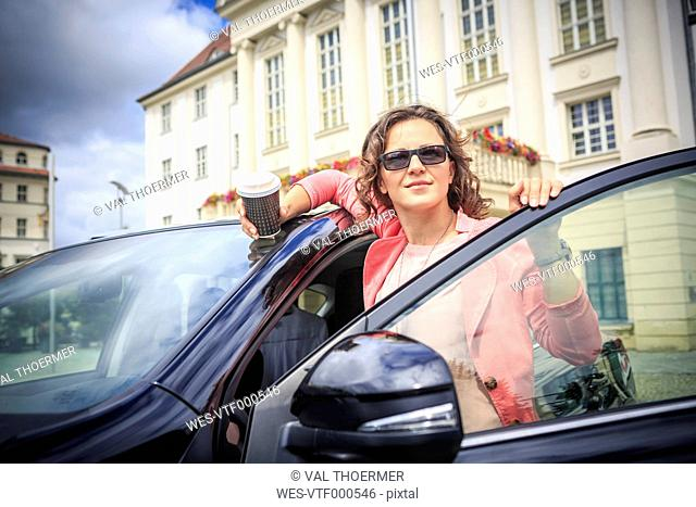 Portrait of woman wearing sunglasses getting on her car