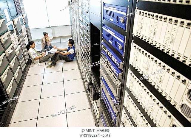 Three multi-ethnic technicians working in a large computer server room