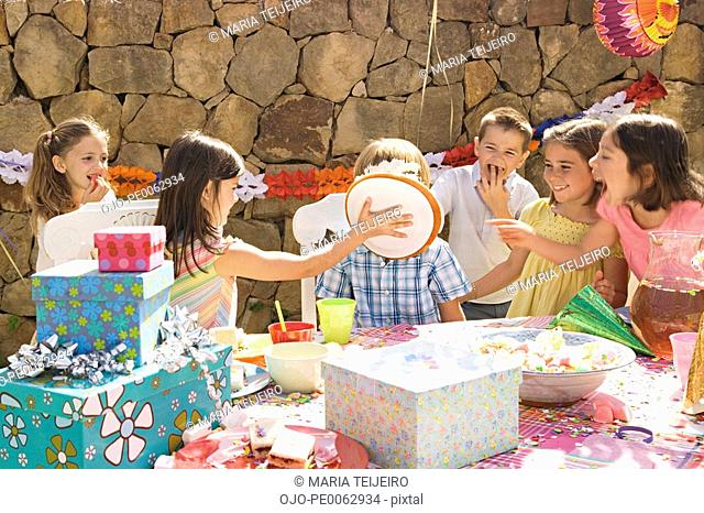 Girl hitting boy in face with pie at birthday party