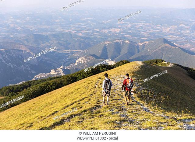 Italy, Monte Nerone, two men hiking on top of a mountain in summer