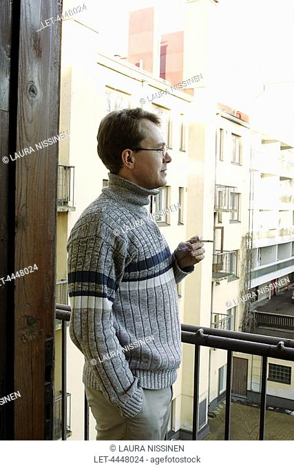 Man smoking on a balcony in Helsinki on January 12, 2005  Finnish Ministry of Social Affairs and Health plans to outline changes to the tobacco law that would...