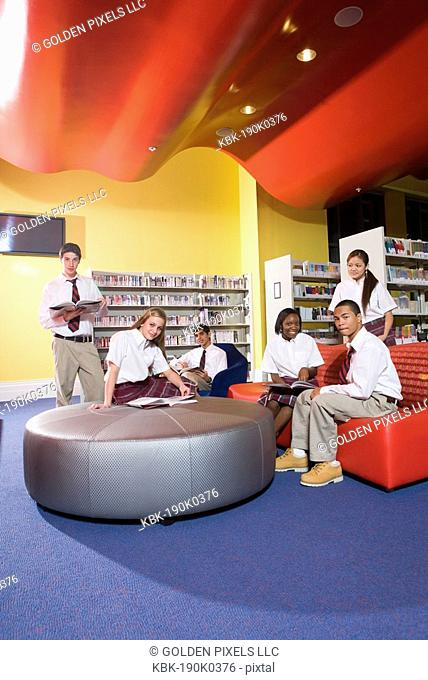 Group of high school students hanging out in library
