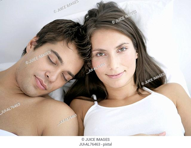 Portrait of a young woman smiling as her boyfriend sleeps on her shoulder