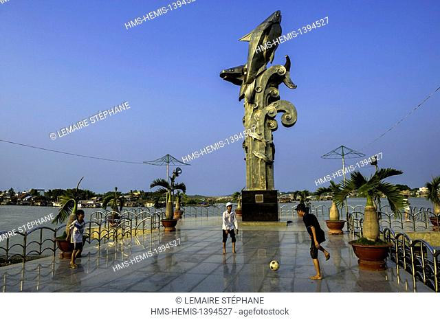 Vietnam, An Giang Province, Mekong Delta region, Chau Doc, young people playing football in front of the emblem of Chau Doc a sculpture of Fish Panga