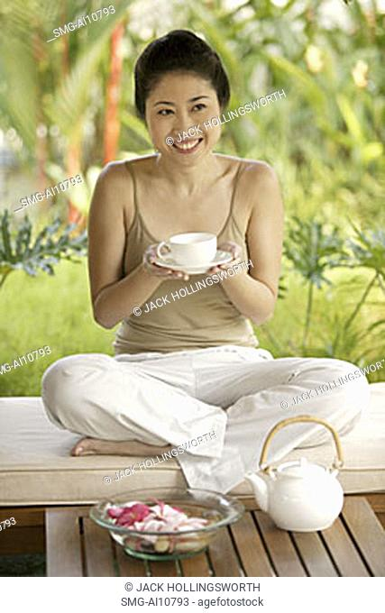 Young woman holding teacup, portrait