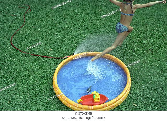 Girl jumping out of Paddling Pool - Garden - Summer