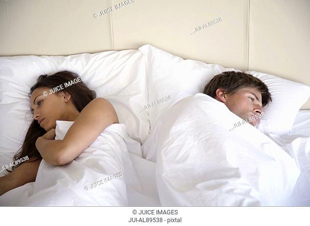 Couple laying with backs to each other in bed