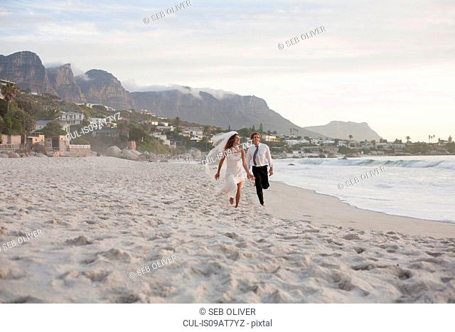 Bride and groom running along beach
