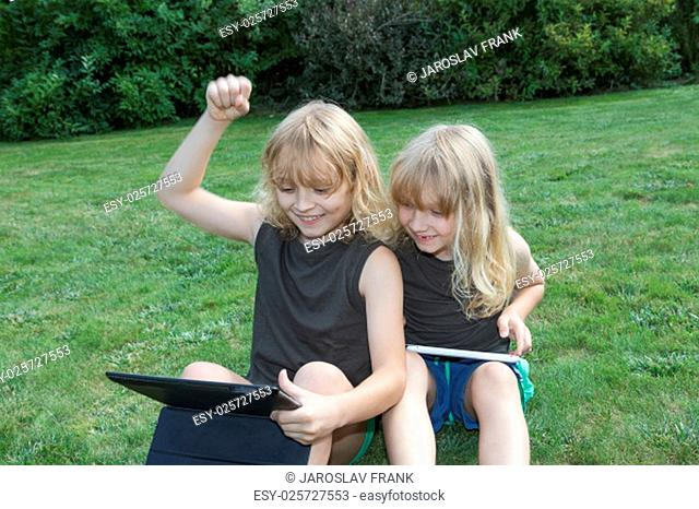 Two blond brothers are sitting on the lawn and playing games on the tablets. Boy sitting on the left is winner. He has raised his left hand