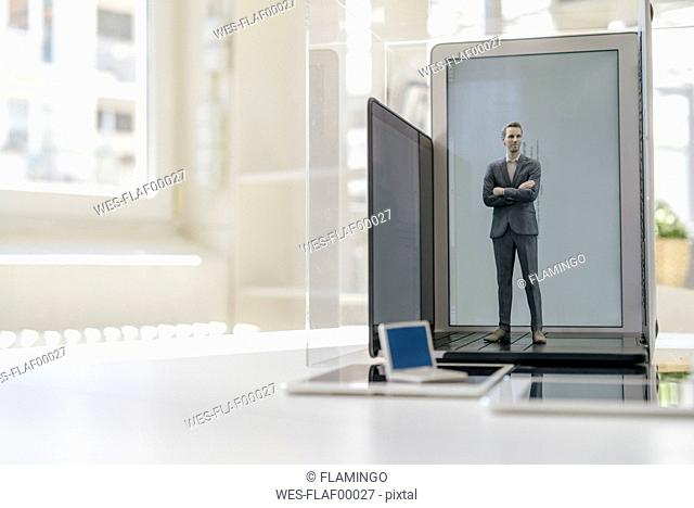 Businessman figurine standing on portable devices in a glass cage