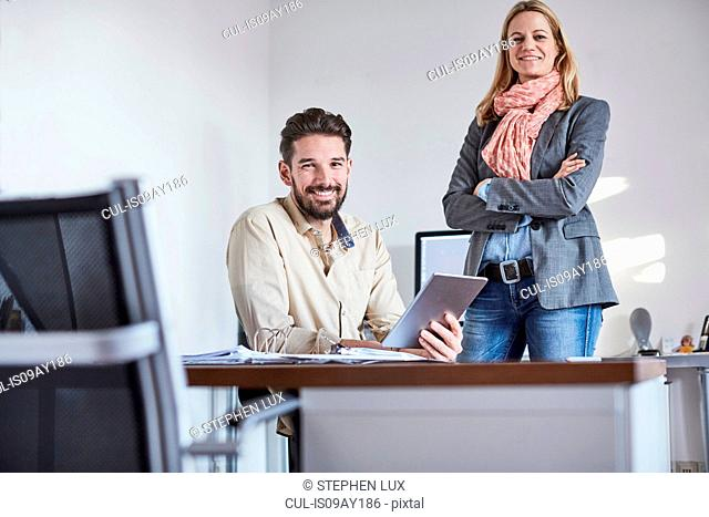 Colleagues in office using digital tablet looking at camera smiling