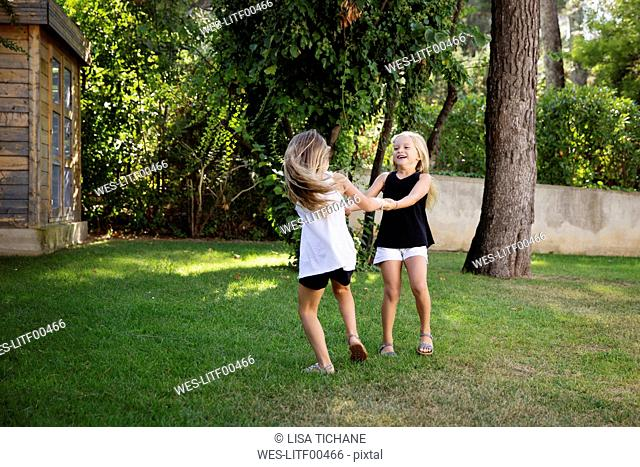 Two little sisters playing ring-a-ring-a-roses in the garden