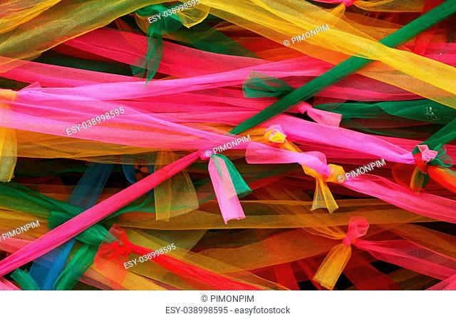 Strips of different colored fabric ribbons decorate a bodhi tree at the Temple in Thailand