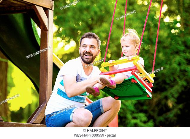Portrait of happy father with his little daughter sitting on a swing of playground