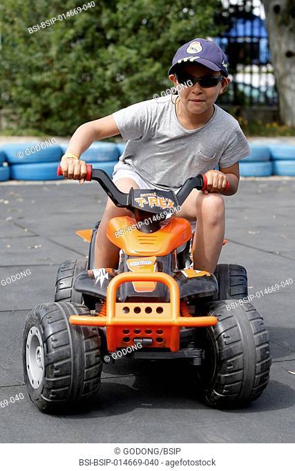 8-year-old boy riding a toy quad