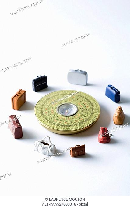 Miniature suitcases and bags arranged around Feng Shui compass