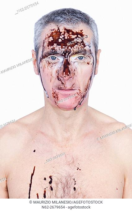 Portrait of a man with a brown liquid dripping from his face he is shirtless
