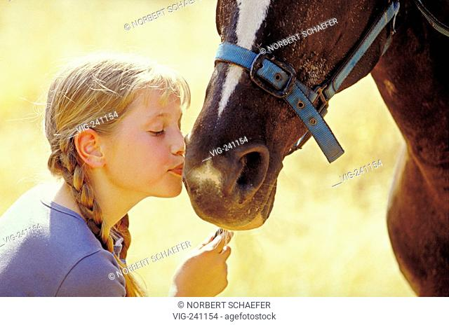portrait, close-up, girl, 12 years, with long blond plaits kisses the nostrils of her horse  - GERMANY, 25/01/2004