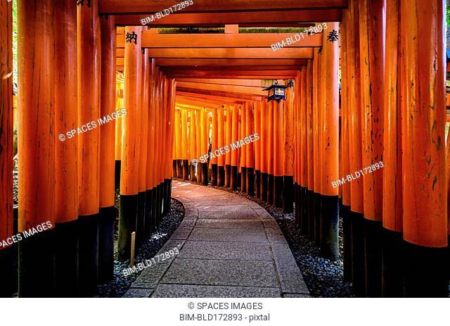 Walkway under orange wooden pillars