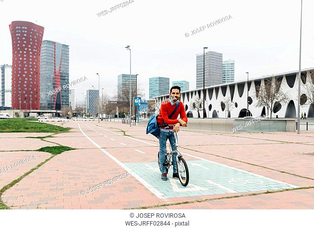 Casual businessman commuting in the city, using his folding bike