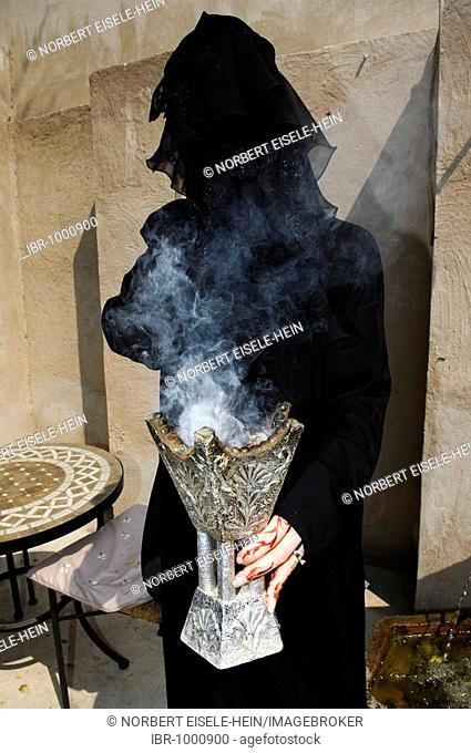 Woman with henna-painting holding incense holder in her hands, Dubai, United Arab Emirates, Middle East